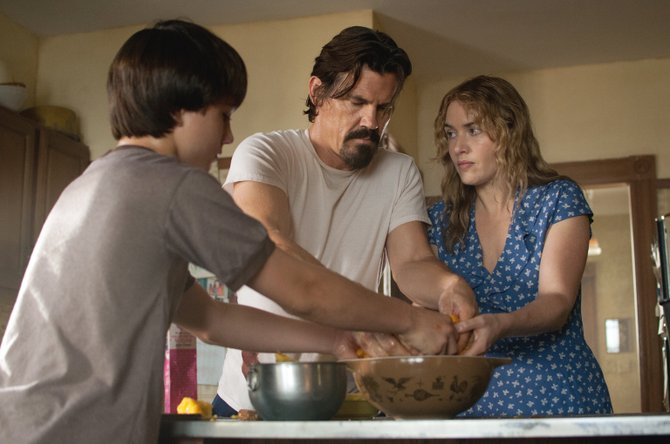 "Frank Chambers (Josh Brolin) shows Adele and Henry Wheeler (Kate Winslet, Gattlin Griffith) how to make a peach pie in ""Labor Day."" The movie is about a boy and his withdrawn mother in 1987 who take in an escaped convict."