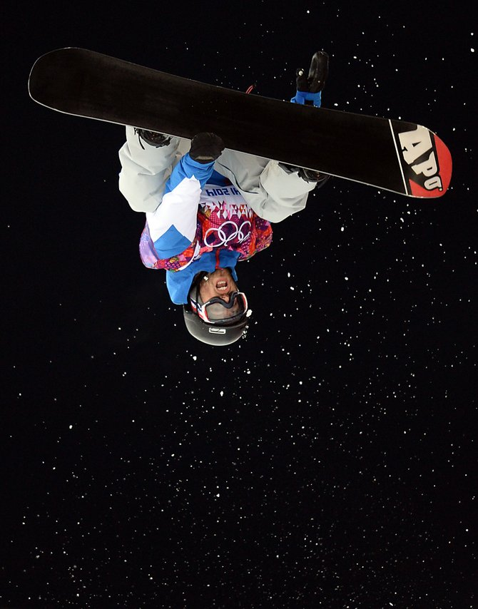 A snowboarder gets heels over head Monday during the half-pipe training session at the 2014 Winter Olympics.
