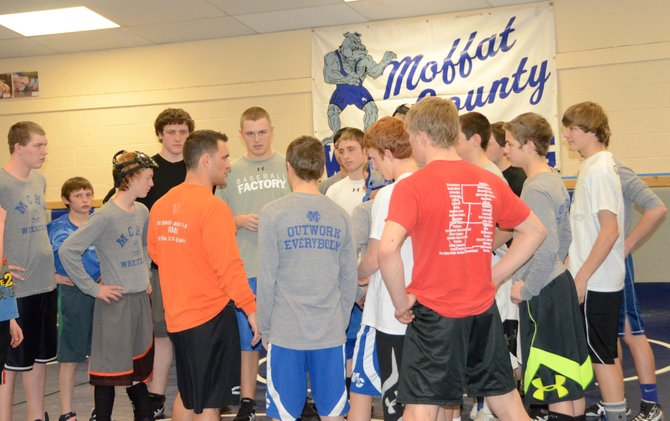 Moffat County wrestling coach Tanner Linsacum, in orange, addresses the team at the beginning of Wednesday's practice. The Bulldogs go to the regional meet in Granby this weekend with hopes of advancing to the state tournament Feb. 20 to 22.