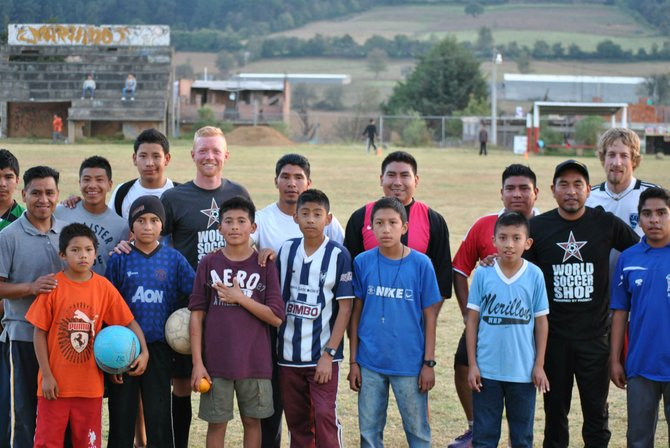 Roddy Beall, left, and Brian Morgan, right, stand with kids from a soccer session in Cherán, Michoacan, Mexico.