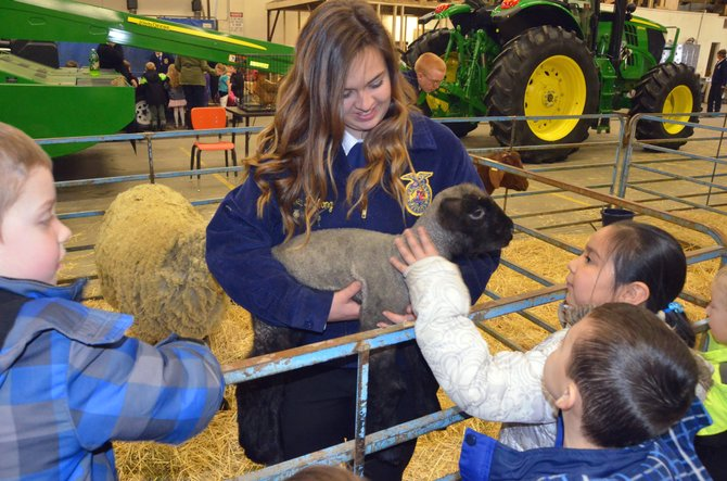 Moffat County High School junior Jerica DeLong holds up a lamb for the students of Ridgeview Elementary School to feel its fleece. DeLong and other members of FFA showed local kindergarten students many parts of agriculture Wednesday for Barnyard Day as part of National FFA Week.