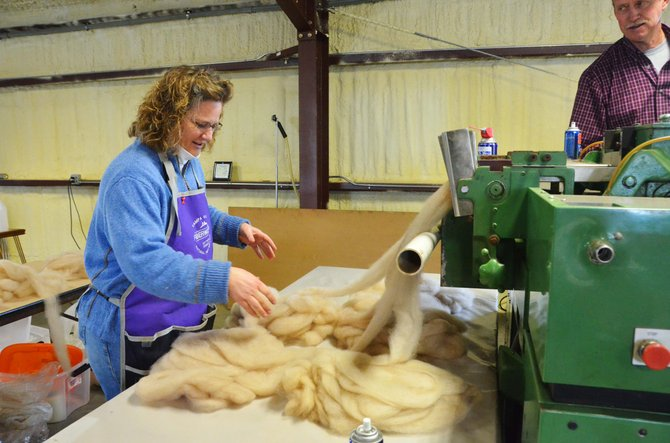 Lewis and Lorrae Moon run fleece through a machine that aligns and twists fibers for a stronger product.