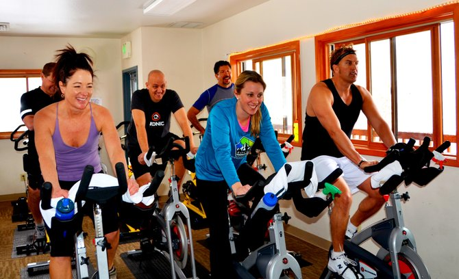 Workout enthusiasts ride fitness bikes at Old Town Hot Springs. Local trainers say one of the keys to keeping a New Year's workout resolution is to not overdo the routine.
