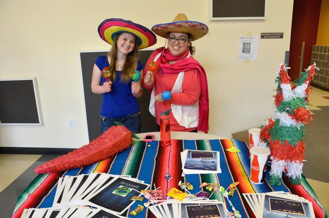 Moffat County High School juniors Abi Gonzales, left, and Carmen Carrasco display sombreros, piñatas, maracas at their booth at Craig Middle School displaying the MCHS Spanish program. Numerous clubs, classes and teams spoke with eighth-graders about what kind of activities will be available to them starting this fall.