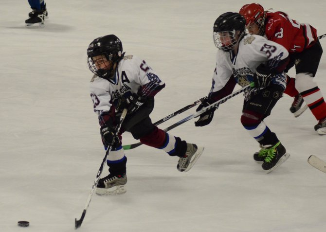 Clay Durham chases down the puck in the neutral zone Thursday in Craig. The Cougars Squirt-age team (10 and under) lost to Steamboat 9-0 in its Continental Divide Youth Hockey League game.