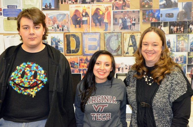 DECA adviser Krista Schenck, right, and Moffat County High School seniors Bob Meyers, left, and Elisa Teeter take a break in Schenck's classroom during lunch. Meyers and Teeter were among the students who competed at the state level for DECA last weekend and will also compete on behalf of MCHS's FBLA team in April.