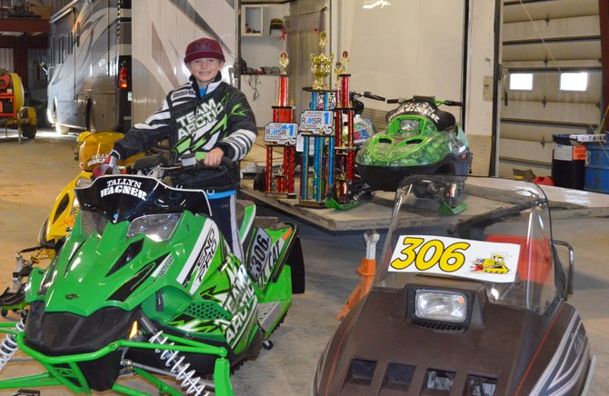 Tallyn Wagner sits with his array of snowmobiles and Snocross trophies. In the Rocky Mountain Snowmobile Racing 2014 season, the 8 year old from Craig has gone undefeated against other riders his age.