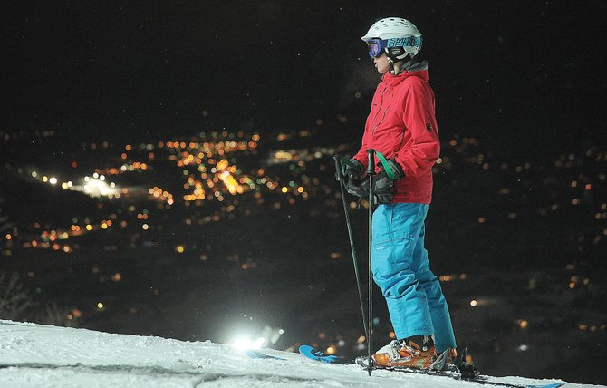 Andrew Petersen waits for friends at the top of the Christie Peak Express lift earlier this season as the lights of Steamboat Springs create a colorful background. Steamboat Ski Area announced 2014-15 ski pass prices Tuesday and again will be offering night skiing as an add on.