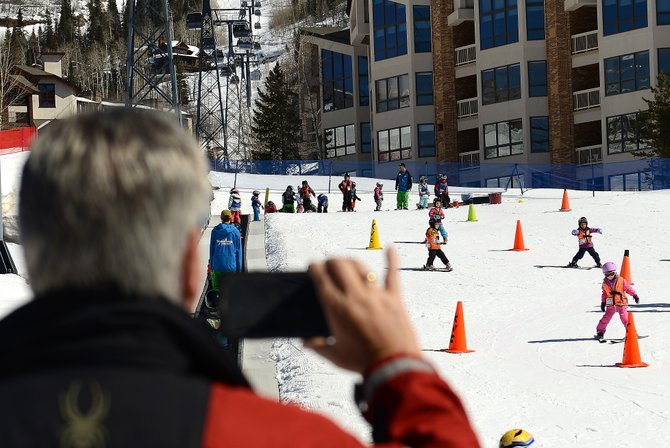 "Mike McPhillips uses his smartphone to video his grandchildren skiing at Steamboat Ski Area on Wednesday. McPhillips, in town from Cocoa Beach, Fla. with his family, was enjoying the week. ""There's more sun here than in Florida,"" he said."