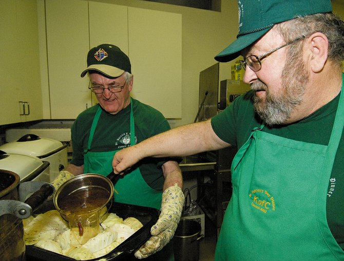Bob Litzau, right, and Bob Brown help with the corned beef and cabbage dinner hosted by Knights of Columbus in 2008. The St. Patrick's Day dinner again will be offered at 5 p.m. Monday at Holy Name Catholic Church.
