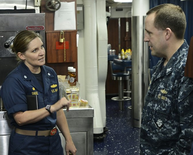 Navy Cmdr. Nicole Shue, commanding officer of the guided-missile destroyer USS Higgins, speaks with Capt. Thomas Workman, commodore of Destroyer Squadron 23, aboard ship in the Arabian Gulf in June 2013. Higgins was deployed to the U.S. 5th Fleet area of responsibility promoting maritime security operations, theater security cooperation efforts and support missions for Operation Enduring Freedom.