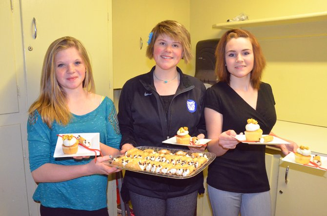 From left, Madysen Cramer, Tané Otis and Felicia Vasquez prepare to serve up cupcakes and cannoli as part of the Bear River Young Life banquet Sunday at the Moffat County Fairgrounds Pavilion. The event allows the community to learn more about the organization, which works with youths in Craig and Hayden.