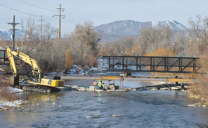 Crews install a pedestrian footbridge in 2011 that connected the Yampa River Core Trail in front of the Depot Art Center to West Lincoln Park. In her state of the city report, City Manager Deb Hinsvark suggested that the city will need a more reliable source of revenue for future capital improvement projects.