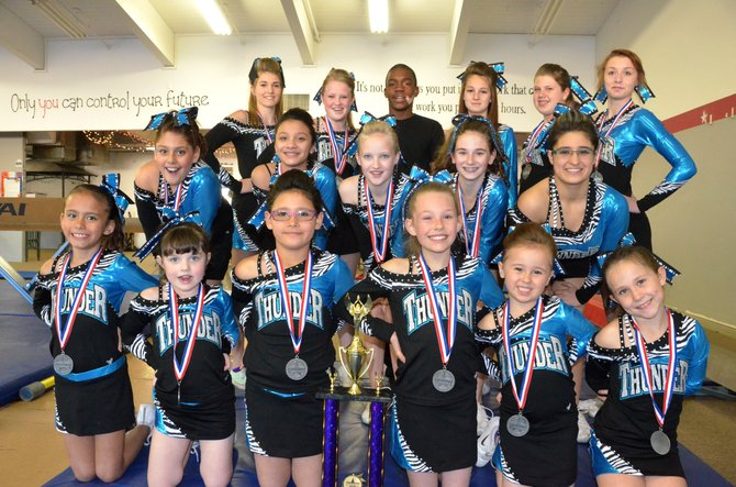 The members of the junior and senior levels of Moffat County Thunder cheer team pose with their medals and trophy in the practice space at Rising Star Youth Training Center. The juniors won second place at a championship event in Denver March 16, and both teams will be attending a national competition in May.