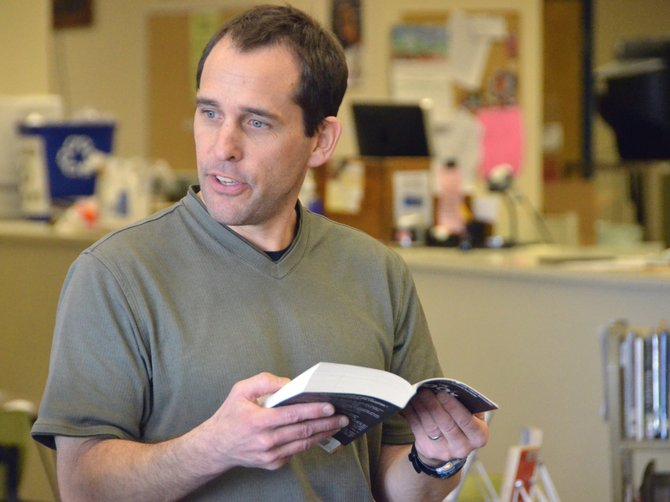 "Moffat County High School librarian James Neton quotes a passage from Markus Zusak's ""The Book Thief"" during the One Book, One MCHS event Tuesday in the school library. Functioning as a book club for students and teachers, the program allowed them to discuss their thoughts on the novel."