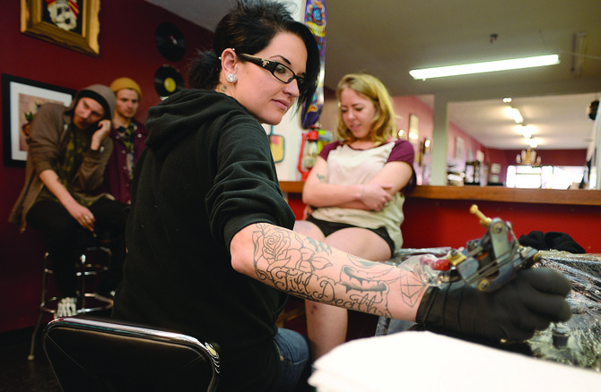 Tattoo artist Melissa Freeman dips the needle of her tattoo gun into a cap filled with ink while working on a tattoo at Deluxe Tattoo in downtown Steamboat Springs.