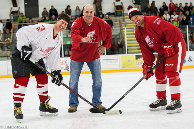Event organizer Chris Campanelli, center, drops the ceremonial puck for fellow organizer Kerry Shea, left, and NHL great Joey Kocur at last weekend's Red Wings alumni hockey game at Howelsen Ice Arena.