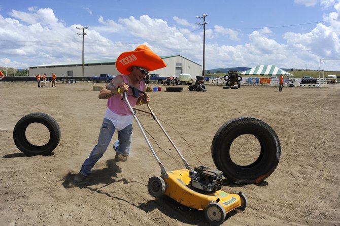 Sean Bailey pushes a lawn mower during the 2013 Routt County Redneck Olympics at the Routt County Fairgrounds in Hayden.