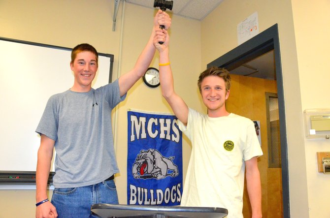 Moffat County High School junior Chris Kling, left, and senior Derek Maiolo hold up a gavel behind a lectern in triumph. The two recently represented the MCHS speech and debate team at state, narrowly missing moving on to the finals.