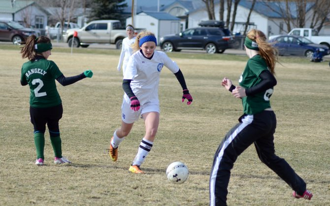 Delaney Baker dribbles between two Rangely defenders Friday at Woodbury Sports Complex. Baker scored three goals for Moffat County in an 8-0 win.