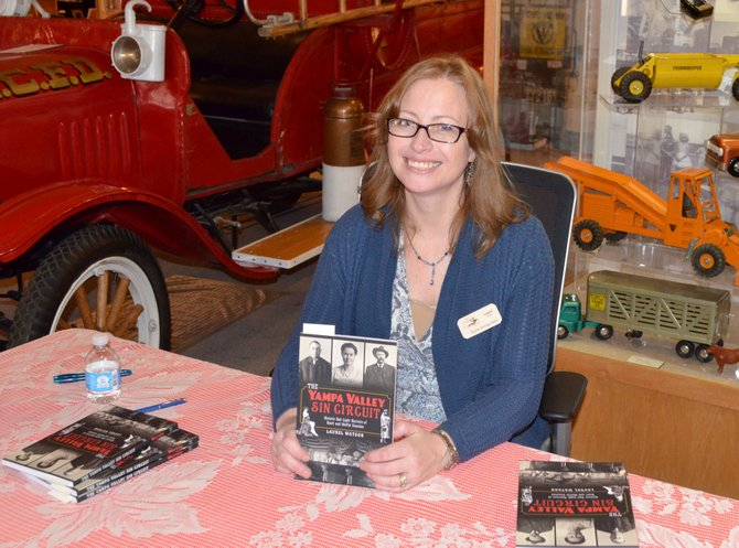 "Laurel Watson, curator of the Hayden Heritage Museum, with her book ""Yampa Valley Sin Circuit: Historic Red-Light Districts of Routt and Moffat Counties"" at the Museum of Northwest Colorado on Saturday."