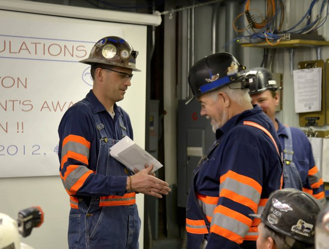 Twentymile Coal Co. Safety Manager Mike Crum presents a thank you letter to Maintenance Supervisor Mike Murphy during the presentation of the President's Award, which recognized the mine as having the best safety record of any of Peabody Energy's underground mines in 2013.