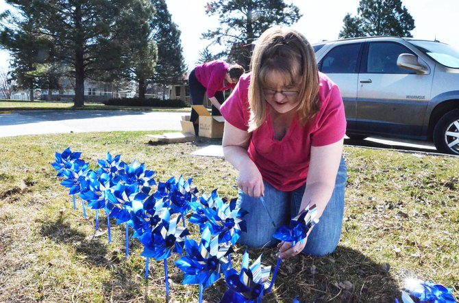 Amanda Arnold, Moffat County United Way community impact coordinator, plants pinwheels for a Connections 4 Kids campaign against child abuse.