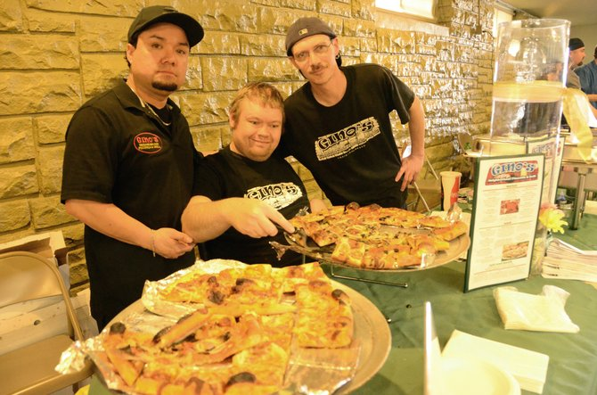 Horizons client Bobby Holmberg joins Gino's Neighborhood Pizzeria & Grill employees Fernando Rojas, left, and Justin Bingham, right, during Thursday night's Pick-a-Dish fundraiser. Eight Craig restaurants provided food for the event, while those involved with Horizons helped with preparation and service.