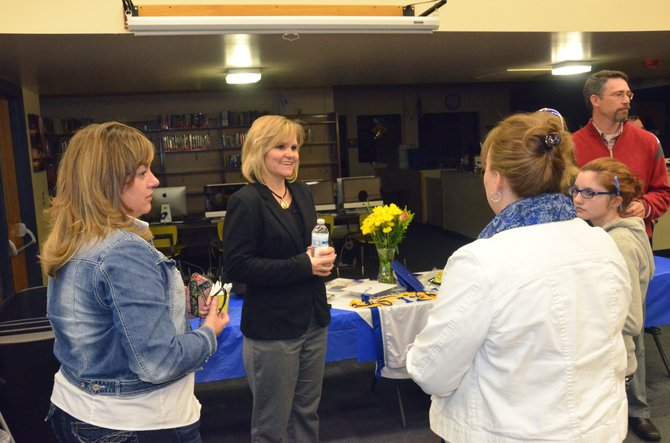 Danielle Van Esselstine, center, chats with parents, teachers, students and other community members Monday evening in the Moffat County High School library. Van Esselstine is one of four candidates being interviewed this week to fill the principal position at MCHS.