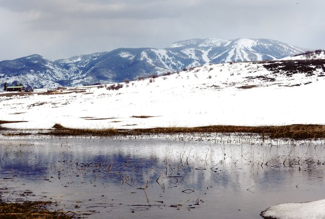 The ski slopes of Steamboat Ski Area are reflected in a small pond formed in a pasture west of Steamboat. For the 2014-13 season, a total of 346 inches fell at mid-mountain and 409.5 inches at the summit.