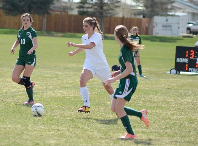 Brenna Ciesco dribbles past Colorado Rocky Mountain School defenders Thursday at Woodbury Sports Complex. Moffat County narrowly beat the Oysters in a game it needed, 5-4.