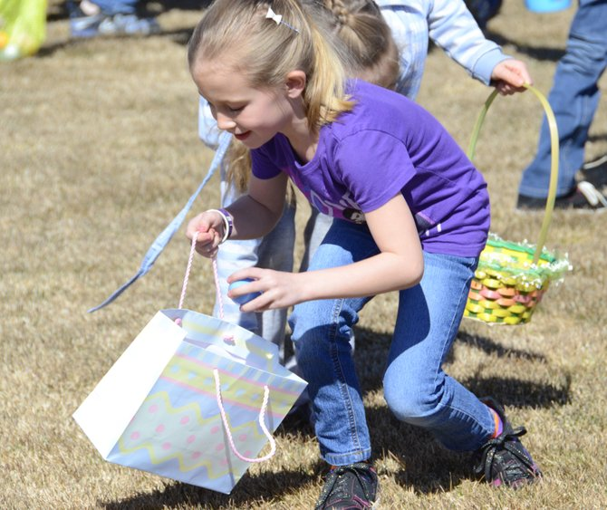 Skyler Coleman, then age 7, puts an egg in her basket at the 2013 Easter egg hunt at New Creation Church in Craig. This year's event is at 11 a.m. Saturday.