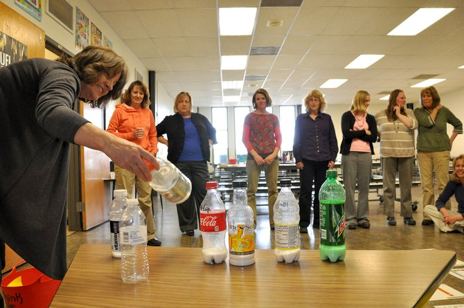 Dietitian Karen Massey shows a group of teachers in Hayden how much sugar is in popular sodas and other drinks. The lesson was part of a new cooking class in Hayden that is helping educators in the school district to shop and cook healthier.