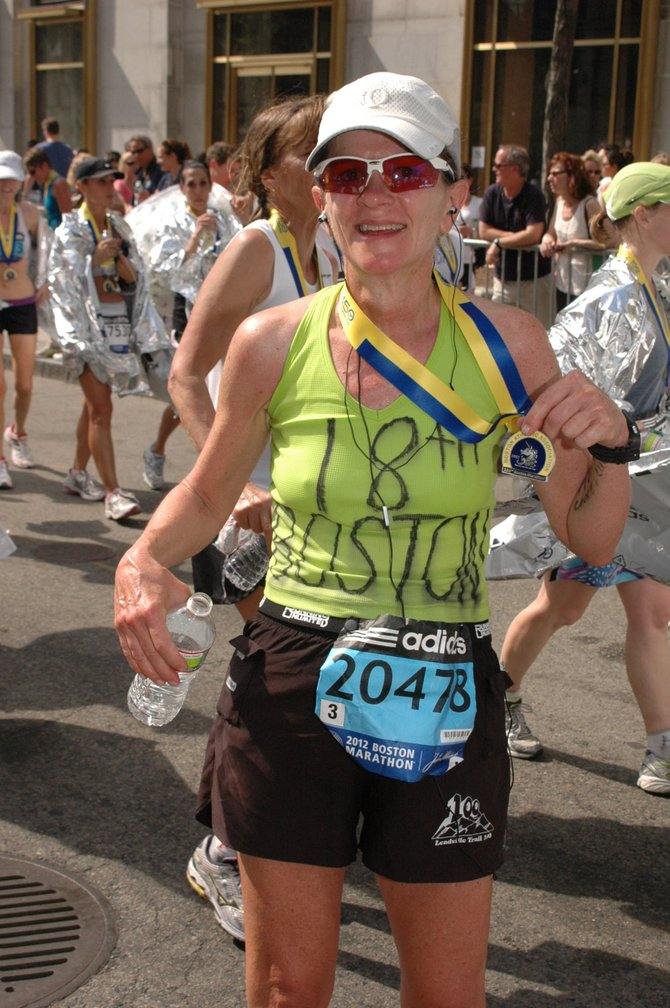 Jennifer Schubert-Akin shows off her medal in 2012 after finishing her 18th Boston Marathon. Her 19th, last year, was marred by a pair of bombings that killed three at the race and paralyzed the region. She didn't hesitate to return to the race this year for her 20th running, however.