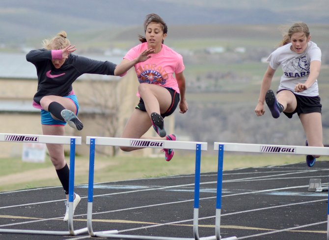 Karmen Christopher (left), Selena Hernandez (center) and Ashlee Griffiths work on their hurdling Tuesday at the MCHS track. The Bulldogs are hosting the Clint Wells Invitational in Craig this Friday.
