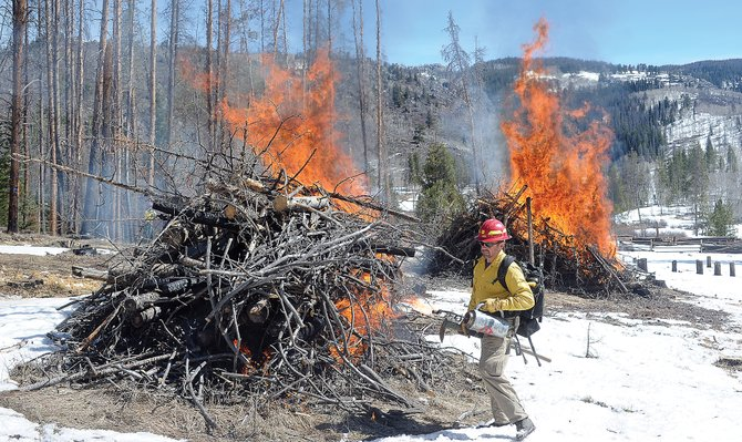 U.S. Forest Service Zone Fire Management Officer Sam Duerksen uses a drip torch to start several piles of slash material on fire Thursday morning in the Lynx Pass area. The controlled burn was part of a joint effort with a private landowner to clean up and create access to a firebreak in an area known for wildfires. Duerksen said the cleanup will make fighting fires in the future easier and should make access in and out of the area safer in the case of a wildfire.