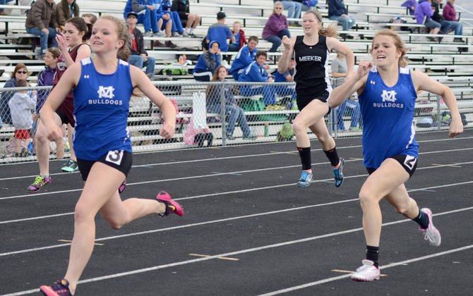 Emma Samuelson (left) and Cheianne Pinnt come down the home stretch of the Moffat County track Friday at the Clint Wells Invitational. The two took first and second in the 200-meter dash here and were teammates on the Moffat County girls 800-meter relay, which won the meet.