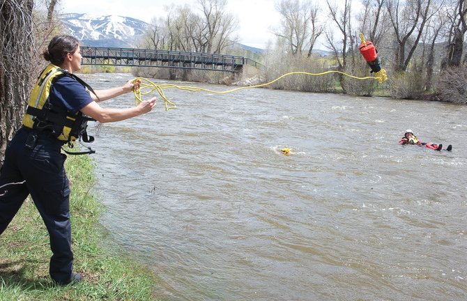 Steamboat Springs Fire Rescue's Julie Wernig runs through a swift water training session with her fellow firefighters in 2013 on the banks of the Yampa River. Routt County Search and Rescue is asking that with more people thinking about floating the town stretch of the Yampa River, unnecessary searches can be avoided if people who lose their watercraft place a call to emergency officials.
