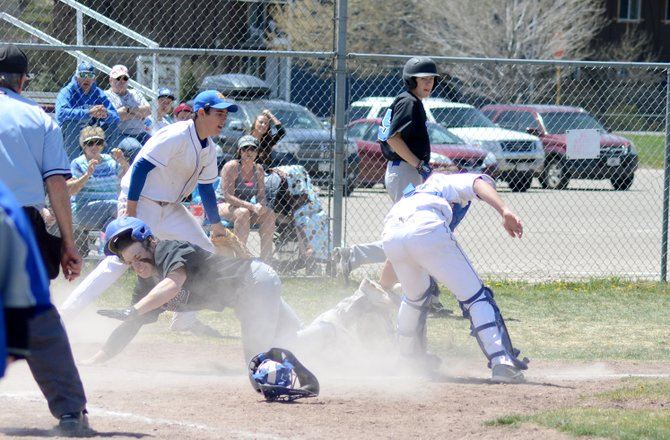 Brett Loyd reaches for home plate while the throw to home plate comes in behind him Saturday in Craig. Loyd hit a single, then scored from first-base on an error to give the Bulldogs a dramatic 15-14 walk-off win against the Rams in the first game of their double header.