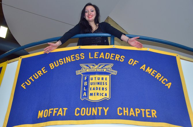 Moffat County High School senior Elisa Teeter displays the banner for the school's chapter of Future Business Leaders of America. Teeter, the outgoing president of FBLA and DECA, recently placed first in Business Procedures at FBLA's state event, the first MCHS student to rank that high. She will attend the national competition in June in Nashville, Tennessee.