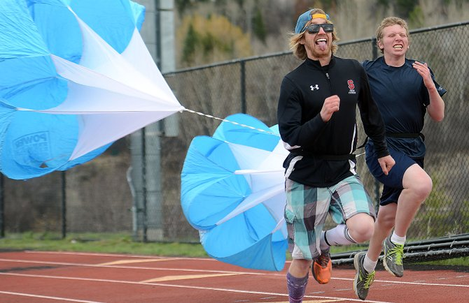 Steamboat Springs High School track coach Erik Ramstad races with a parachute during a recent practice. The track team had 34 athletes out this season and hopes that can be a springboard to the future.