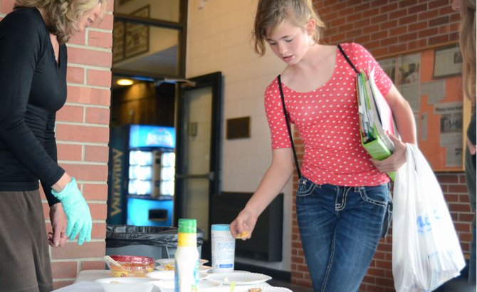 Hayden seventh-grader Faith Day tests some whole-grain chips and hummus at health and wellness coordinator Kristi Brown's taste-testing booth Monday after school. Starting July 1, the U.S. Department of Agriculture is enforcing its strictest school snacks regulation in more than three decades.