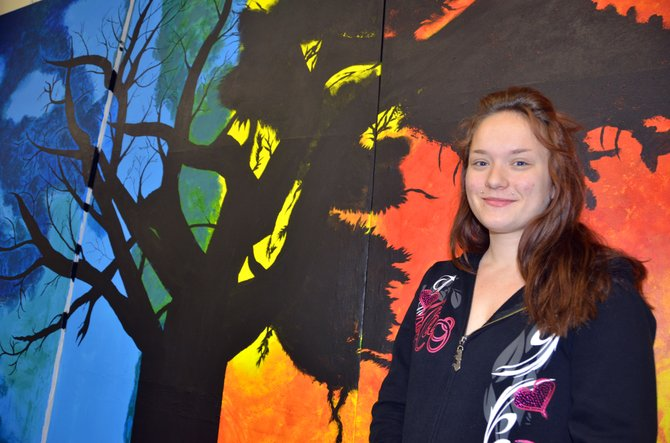"Moffat County High School senior Tanisha Young displays the nearly-completed backdrop that will be shown at MCHS graduation. The depiction of an aging tree at night and a younger one in daylight, painted by Young, Faith Christiansen, Taylor Dean, Yolibeth Molina and Sitclali Nevarez, shows the passage of time and reflects the motto for Class of 2014: ""Don't fear for tomorrow, Don't regret the past, Live for what is now, and Never look back."""