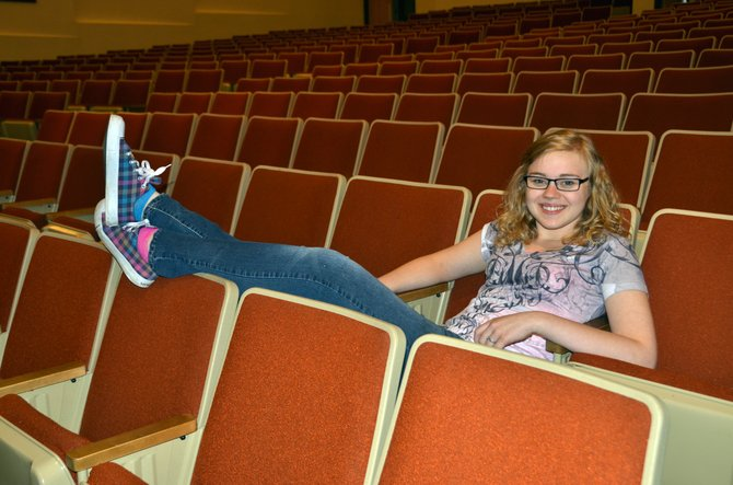 Faith Christiansen takes it easy in the empty Moffat County High School auditorium. Christiansen, a graduating senior and a regular part of MCHS drama and choir, was accepted to the American Musical and Dramatic Academy this year. While she may be unable to afford the full program at the moment, she intends to study theater whatever school she attends.