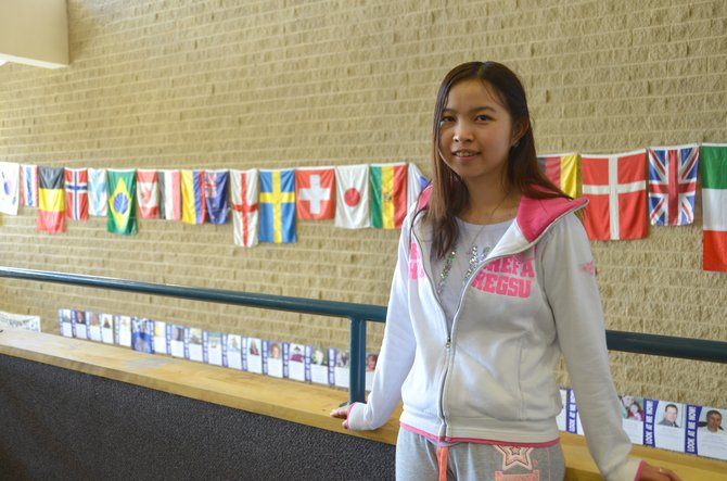 Moffat County High School junior My Nguyen poses among the many international flags on display at Moffat County High School. Nguyen is graduating a year early and will also soon receive an associate's degree from Colorado Northwestern Community College before attending Colorado State University this fall. She is originally from Vietnam, relocating to the United States several years ago.