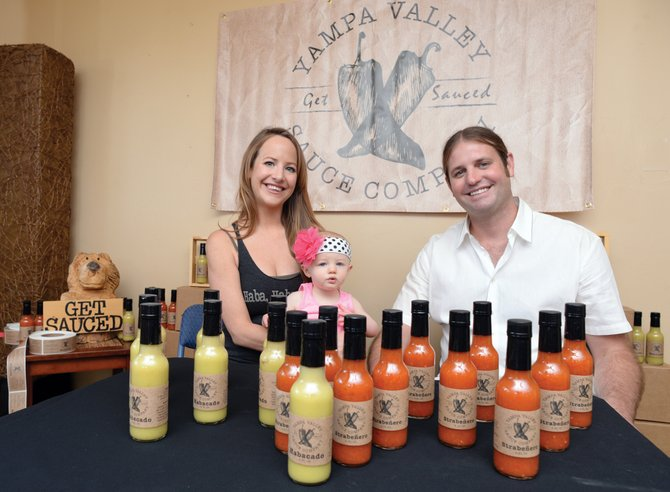 Tami Summy and Clay Meers, along with their daughter Charli, are seen in their home office for Yampa Valley Sauce Co., which they started in order to combine the flavors they wanted on their own food but were otherwise unable to find. Their two signature sauces are Habacado and Strabenero, combinations of habanero and avocado and strawberry, respectively.
