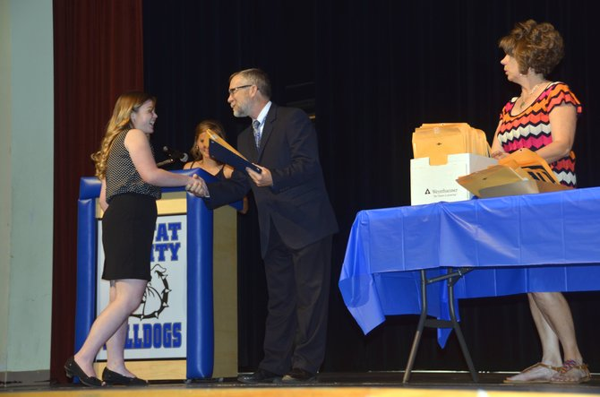 Moffat County High School graduating senior Nicole Ferree, left, accepts a packet of awards from MCHS Principal Thom Schnellinger during the school's awards night festivities.