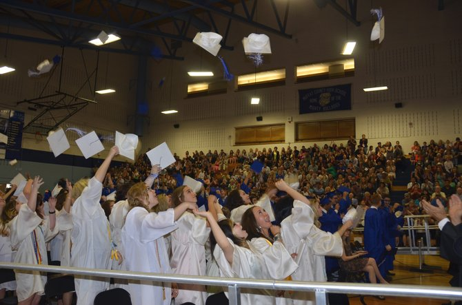 The students of Moffat County High School's Class of 2014 throws caps into the air as their graduation is made official Saturday morning in the MCHS gym. The class consisted of 101 seniors and early graduates.