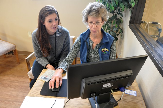 Northwest Colorado Visiting Nurse Association community and small-business insurance coordinator Erin Gleason, left, helps LIFT-UP of Routt County Assistant Thrift Store Manager Nancy Mayer shop for a new health insurance plan last year. A change in the state's insurance rating map could result in higher premiums on the marketplace for Routt County.
