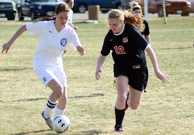 Allie Ehlers tries to dribble past a Grand Valley defender this spring at Woodbury Sports Complex. Ehlers has been a key player on the volleyball, basketball and soccer teams for Moffat County since she moved to Craig two years ago.
